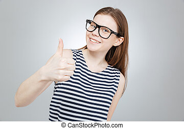 Happy beautiful teenage girl in glasses shpwing thumbs up...