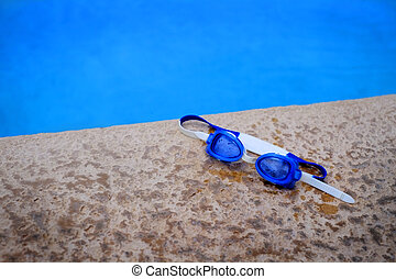 Blue Swim Goggles Next to Swimming Pool