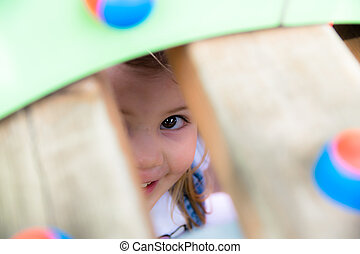 Little girl playing hide and seek. - Little girl playing...