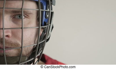 Closeup Portrait of a Hockey Player in Helmet against White...