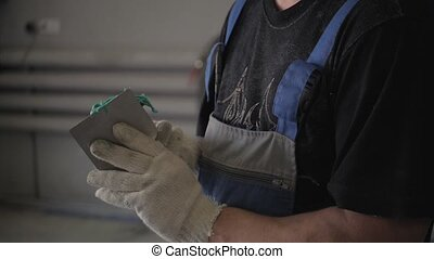 Repairman is Preparing Car Putty in Service - Repairman is...