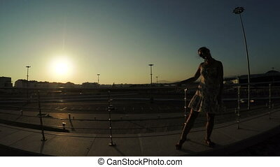 Silhouette of girl gymnast - In sun backlit Olympic Park...