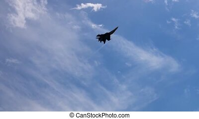 Fighter plane making barell-roll against blue sunny sky -...