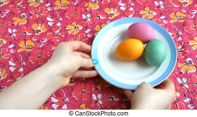 She puts on a pink tablecloth saucer with colorful eggs and...