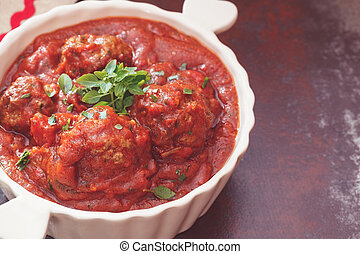 Meatballs with spiced tomato sauce in a casserole dish....