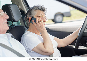 Elderly lady using mobile phone while driving