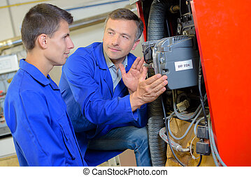 Tutor showing apprentice the width of electrical box