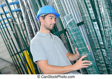 Man selecting shrink wrapped pack of poles