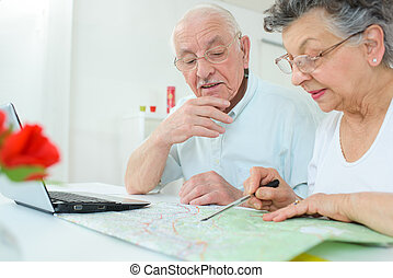 elderly couple mapping the route
