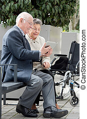 elderly couple with a tablet
