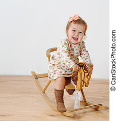 Little girl and horse - rocking chair. Studio shot