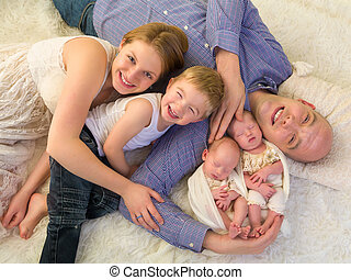 Happy family with newborn twins - Happy parents posing with...