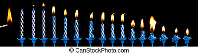 Row of burning birthday candles and match stick on a black...