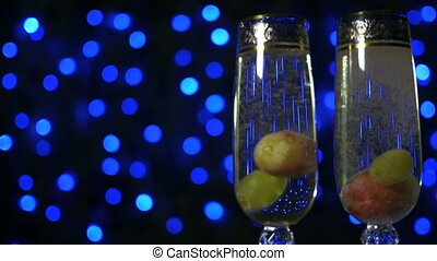 Green grapes falling into glass of golden bubbling champagne