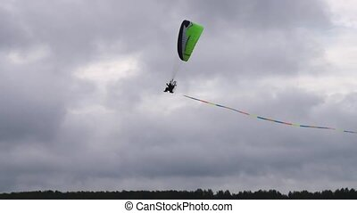 Paragliding against cloudy sky - Paraglider flying against...