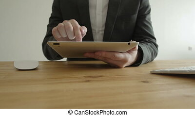 Close-up Front View fragment of a Man in a Business Suit Working with the Tablet Pad Device, Laptop with Graphics
