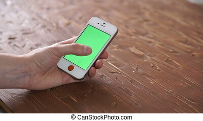 Using smart phone on wood table various hand gestures,...