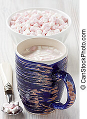Hot cocoa beverage in blue rustic mug with marshmallow...