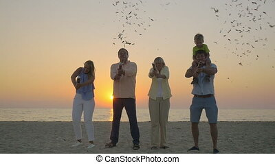 Family celebration with confetti on the beach - Slow motion...