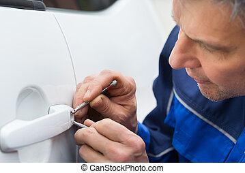 Hand Holding Lockpicker To Open Car Door - Close-up Of...