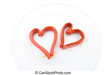 Two Fried sausage in the form of heart on a white background...