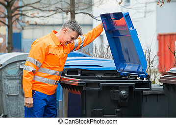 Man Looking In Dustbin On Street - Working Man Looking In...