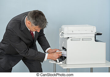 Businessman Removing Paper Stuck In Printer At Office -...