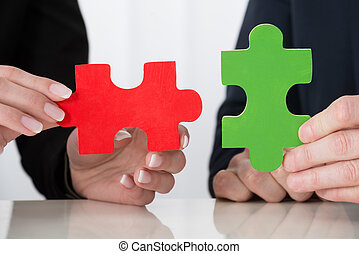 Businessperson Hand Holding Puzzle Pieces