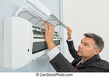 Businessman Checking Air Conditioner Mounted On Wall In Office