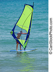 Windsurfer with bright green sail - Male windsurfing with a...