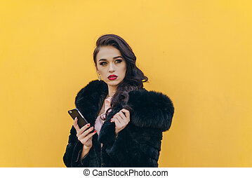 Beautiful girl with the phone on a yellow background -...