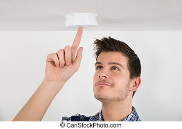 Male Electrician Testing Smoke Detector - Young Male...