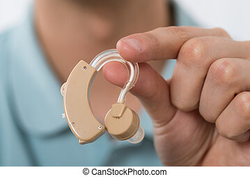 Man Holding Hearing Aid - Close-up Of Man Hand Holding...