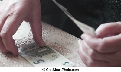 Senior woman hands counting 5 euro banknotes closeup,...