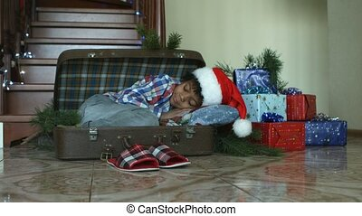 Kid sleeping inside cozy suitcase. Boy's Christmas nap...