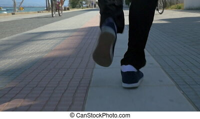Male feet running on sidewalk in resort town - Slow motion...