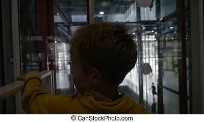 Child riding in modern glassy elevator - Slow motion of a...