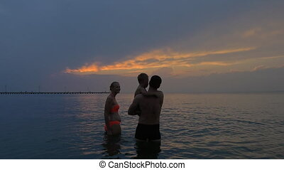 Family with child in the sea at twilight - Slow motion of a...