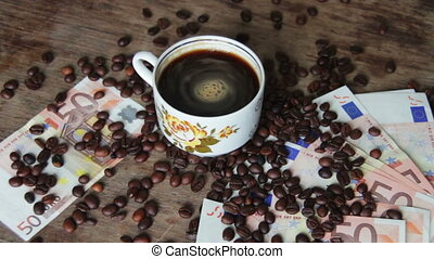 Coffee Beans, Coffee Cup and Euro on a Wooden Table. Coffee...