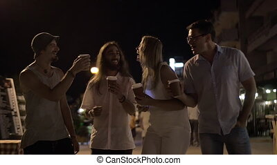 Friends toasting with coffee cups in night street - Slow...