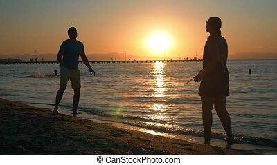 Couple playing tennis on the beach at sunset