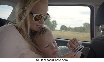 Child playing with mothers smartphone in the car