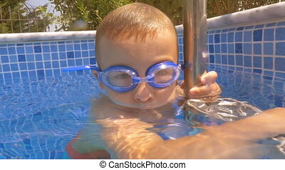 Child diving in the pool on hot summer day