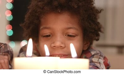 Smiling boy looks at candle.
