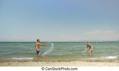 Couple playing ping pong on the beach - Slow motion of happy...