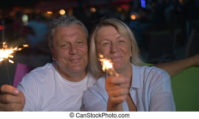 Happy senior man and woman with sparklers - Slow motion of...