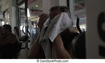 Tired man wiping sweat after workout in the gym - Slow...