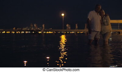 Senior couple and candles in night sea