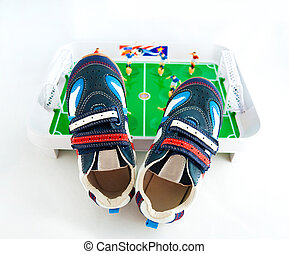 Children\'s sports footwear against a toy football ground