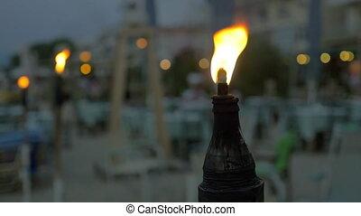 Burning tiki torch at twilight - Slow motion close-up shot...